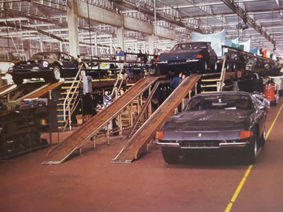 Ferrari built their first assembly line in 1958 to produce the 250 GT models and in 1960 they added a second line. In 1972 the line at left was used exclusively to build 264 GT Dinos while the line at the right produced a mix of V-12 engined 365 GTB/4 and 365 GTC/4 models. Shown here are a long line of 365 GTC/4s with their hoods up behind the sole blue 365 GTB/4 at the front of the line.